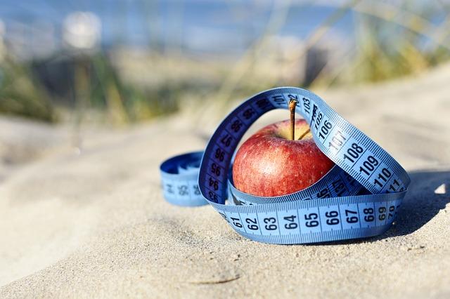 modrý krejčovský metr a jablko